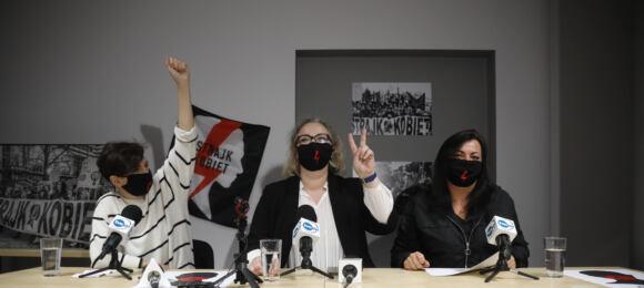 Trzy liderki Strajku Kobiet wczarnych maeczkach zbłyskawicami pokazują znak V, siedząv przy stole zplakatami OSK