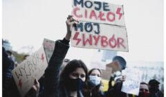 Kobieta trzyma nad głową baner z napisem Moje ciało, mój wybór