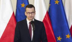 Mateusz Morawiecki na tle flag Polski i UE
