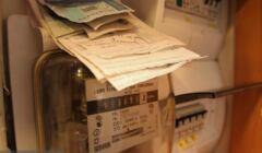 licznik prądu, na którym leżą paragony i plik banknotów