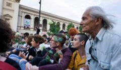 Protestujący siedzą na jezdni Krakowskiego Przedmieścia z białymi różami w rękach