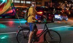 aktywista Kacper Kubiak na rowerze z tęczową flagą