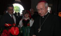 Bronisław Komorowski wręcza kwiaty bp. Dziubie