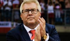 Ryszard Czarneck, w czarnym garniturze i czerwonym krawacie, stoi i klaszcze