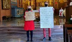 Joann Sceuring-Wielgus z mężem w kościele, stoją w maseczkach w nawie głównej tyłem do ołtarza, w rękach trzymają plakaty o prawach kobiet
