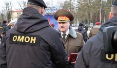 Łukaszenka w wojskowym mundurze i czapce wręcza order funkcjonariuszowi OMON