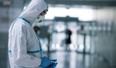 Lekarz w stroju ochronnym patrzy na trzymany w ręce telefon