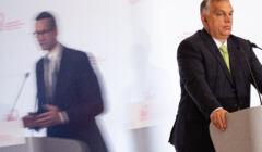 Premier Węgier Orbán stoi na mównicy, z boku odbicie w szybie przemawiającego premiera Morawieckiego