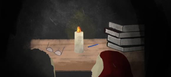 Na biurku nauczycielskim stoi zapalona świeczka