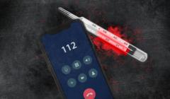 Na pierwszym planie telefon z wybranym numerem 112, w tle termometr z podkreśloną temperaturą