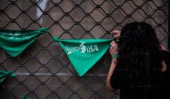 Argentynka wieszająca zieloną chustę z napisem