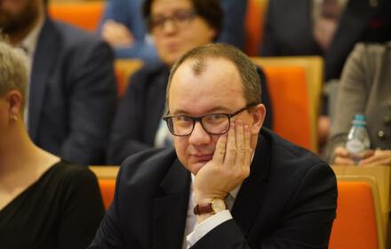 Adam Bodnar, siedzi, głowę podpiera ręką, patrzy w obiektyw
