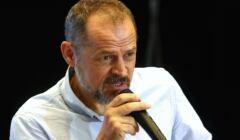Prof. Rafał Wnuk w białej koszuli z mikrofonem w ręku