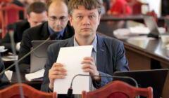 Radny Dyba-Bojarski podczas sesji rady, w ręku trzyma plik kartek