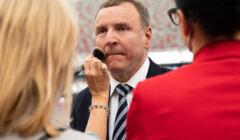 Jacek Kurski stoi, makijażystka pudruje pędzelkiem jego twarz przez konferencją prasową
