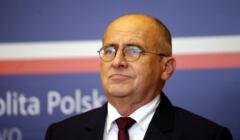 Szef polskiej dyplomacji, Zbigniew Rau na tle niebieskiej planszy z logo MSZ