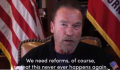 Arnold Schwarzenegger przemawia na tle flagi USA