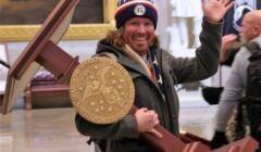 Mężczyzna w czapce z napisem Trump wynosi pulpit z którego przemawia spiker Izby Reprezentatów