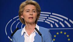 Ursula von der Leyen w błękitneej marynarce i białej bluzce przemawia na tle niebieskiego logo Komisji Europejskiej