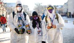 Trójka młodych wolontariuszy w białych skafandrach a białych maseczkach na twarzy z puszkami na pieniądze w rękach