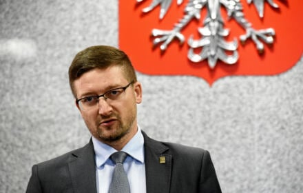 Sędzia Paweł Juszczyszyn na tle polskiego godła