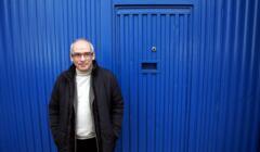 Jan Lityński w kurteczce, z półuśmiechem na tle jaskrawo niebieskiej ściany