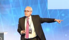 Prof. Nikkos Passa na scenie wykłąda z wyciągniętą lewą ręką