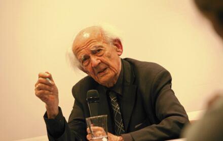 Zygmunt Bauman na scenie z mikrofonem w ręku