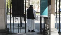 Zakonnik dominikanin stoi tylem w otwartej bramie do kościoław brami