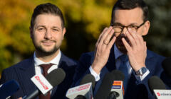 Patryk Jaki stoi obok premiera Morawieckiego, który zasłania dłońmi twarz