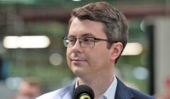Piotr Müller, rzecznik rządu stoi przed mikrofonem