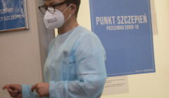 Pielęgniarka wmasce na tle drzwi z napisem Punkt Szczepień