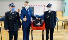 Marcin Warchoł pozuje do zdjęcia ze strażakami