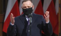 Andrzej Duda w czarnej maseczce rozkłada ręce