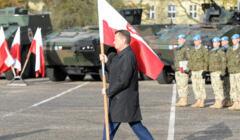 Mariusz Błaszczak niesie polską flagę