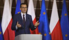 Premier Mateusz Morawiecki na tle polskich i europejskich flag