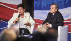 Beata Szydło i Piotr Gliński siedzą na scenie. Szydło trzyma mikrofon