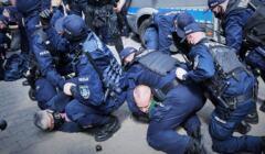 Babcia Kasia na ziemi, twarzą przyciśnieta do chodnika przez policjantów