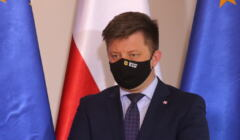Michał Dworczyk w maseczce na twarzy na tle flag polskiej i unijnej