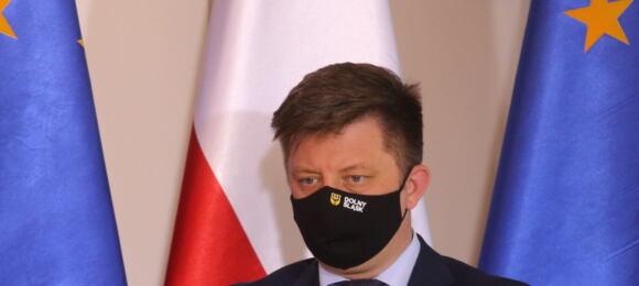 Michał Dworczyk wmaseczce natwarzy natle flag polskiej iunijnej
