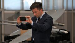 Michał Dworczyk fotofrafujący się na tle bojowego drona