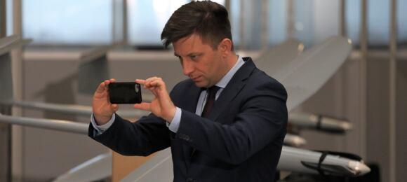 Michał Dworczyk fotofrafujący się natle bojowego drona