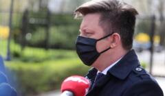Michał Dworczyk w maseczce rozmawia z dziennikarzami przed budynkiem KPRM
