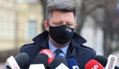 Michał Dworczyk, przed nim kilka mikrofonów logo różnych mediów