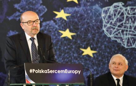 Legutko na trybunie przemawia, Kaczyński siedzi i patrzy na niego zadowolony