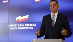 Mateusz Morawiecki przemawia na tle logo Kancelarii Premiera RP
