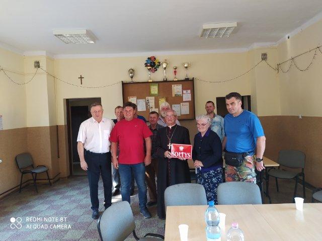"""Arcybiskup trzyma tabliczę z napisem """"Sołtys"""""""