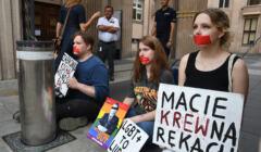 """Trzy osoby przykute do bramy Ministerstwa Edukacji i Nauki z transparentami """"LGBT+ to ludzie"""" i """"Macie krew na rękach"""" oraz wizerunkiem Przemysława Czarnka na tęczowym tle. W tle policjant, ochroniarz i osoba pracująca w ministerstwie"""