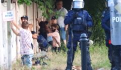 Nastolatki klęczące pod płotem z drutem kolczastym, pilnowane przez uzbrojonych policjantów