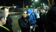 Ludzie z dziećmi na rękach na peronie w nocy